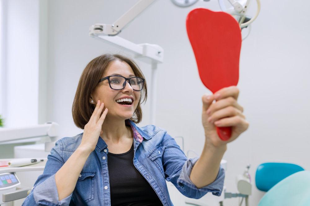 Melrose dental office | Woman smiling at mirror.